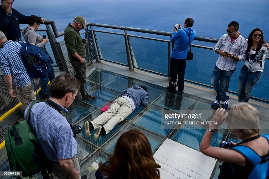 A tourist lies on a glass floor lookout on the top of a cliff to take pictures of Cabo Girao in Camara de Lobos, on Madeira island on April 30, 2016. An 81 years old French tourist died today after falling into a 100 meters deep ravine while he was trekking on the hills of Camara de Lobos, in the Portuguese island of Madeira, firefighters said. / AFP / PATRICIA