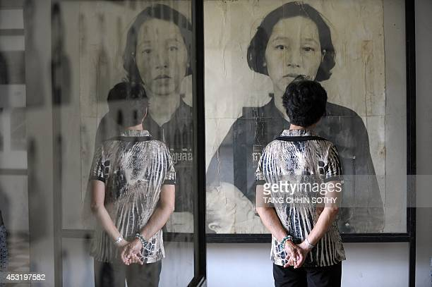 A tourist look at a portrait photo of a victim of the Khmer Rouge on display at the in Tuol Sleng genocide museum in Phnom Penh on August 5 2014...