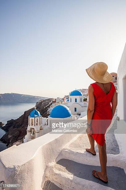 Tourist looking at blue churches, Oia, Santorini