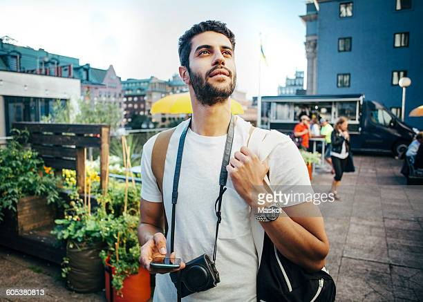 Tourist looking away while holding smart phone during vacation