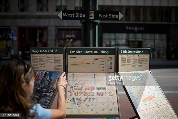 A tourist looks at a map in front of the Empire State Building in New York US on Wednesday June 26 2013 An unidentified bidder offered to buy New...
