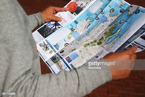 A tourist looks at a map of downtown Sydney in Sydney Australia on Tuesday July 21 2015 Tired hotels outdated attractions like Sydney's Darling...