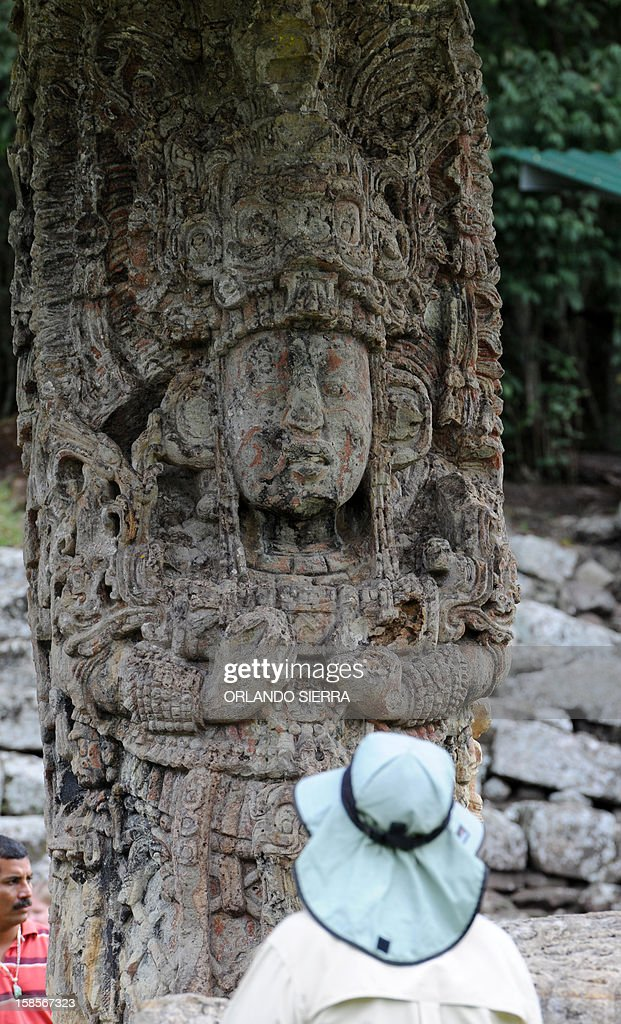 A tourist looks at a Mayan stele at the Copan archaeological park, 400 km northwest of Tegucigalpa, on December 19, 2012. Honduras is one of five countries preparing to celebrate on December 21, the end of the Maya Long Count Calendar --Baktun 13-- which began in 3114 BC. AFP PHOTO/Orlando SIERRA