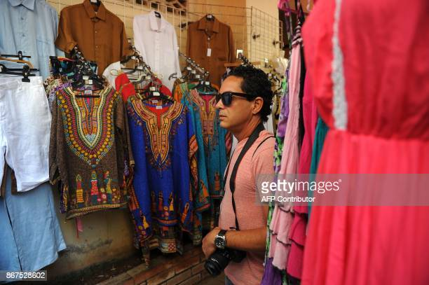 A tourist looks at clothes at a craft shop in Havana on October 27 2017 Almost drowned by the crisis of the 90s the emerging Cuban fashion begins to...