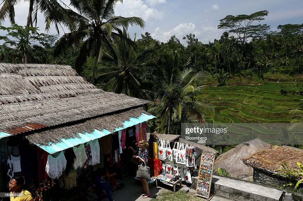 A tourist looks at clothing at a store in front of the Tegallalang rice terraces in Ubud, Bali, Indonesia, on Tuesday, Oct. 8, 2013. Bank Indonesia said it will regulate currency hedging by individuals and companies, including state-owned firms, to help stabilize Asias most-volatile currency. Photographer: SeongJoon Cho/Bloomberg via Getty Images