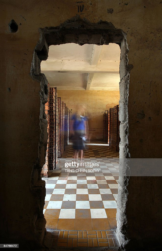 A tourist looks at compartments at the Tuol Sleng genocide museum in Phnom Penh on February 2, 2009. As dusk falls on Cambodia's capital, security guards at the Tuol Sleng genocide museum huddle together at the ticket office to protect themselves from ghosts.