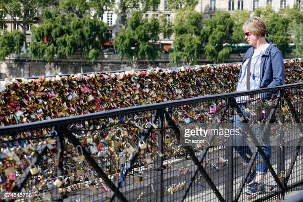 A tourist looks at Love padlocks on the Pont Neuf on April 29 2017 in Paris France The Paris City Hall will organize on May 13th an auction of love...
