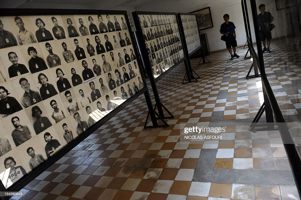A tourist looks at photographs of prisoners on display at the genocide museum at Tuol Sleng, the former prison S-21 used by the Khmer Rouge to imprison and torture thousands of Cambodians during the 1970s, in Phnom Penh on February 10, 2009. Cambodia's UN-backed genocide tribunal will on February 17, 2009 formally open the long-awaited trial of the Khmer Rouge regime's former Toul Sleng prison chief, Kaing Guek Eav, better known as Duch, who is the first of the five leaders detained by the tribunal. Duch, now 66, faces charges of crimes against humanity, war crimes, torture and pre-meditated murder for his role in running S-21, the Khmer Rouge's notorious main prison, during the 1975-1979 regime.