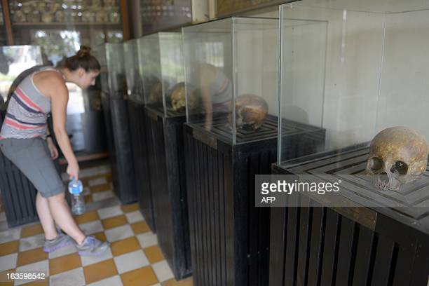 A tourist looks at skulls displayed at the Tuol Sleng genocide museum in Phnom Penh on March 13 2013 A former Khmer Rouge leader on trial for...
