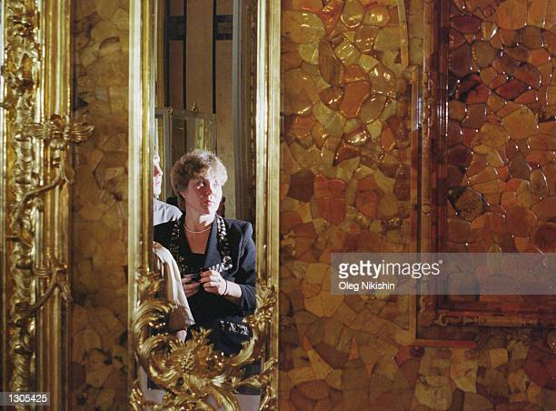A tourist looks at the amber room part of which has been restored by Russian craftsmen July 10 2000 in St Catherine''s Palace in Tsarskoye Selo near...