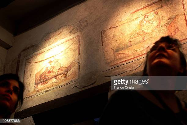A tourist looks at the erotic paintings and graffiti inside the Lupanare on November 14 2010 in Pompeii Italy Pompeii is a partially buried Roman...