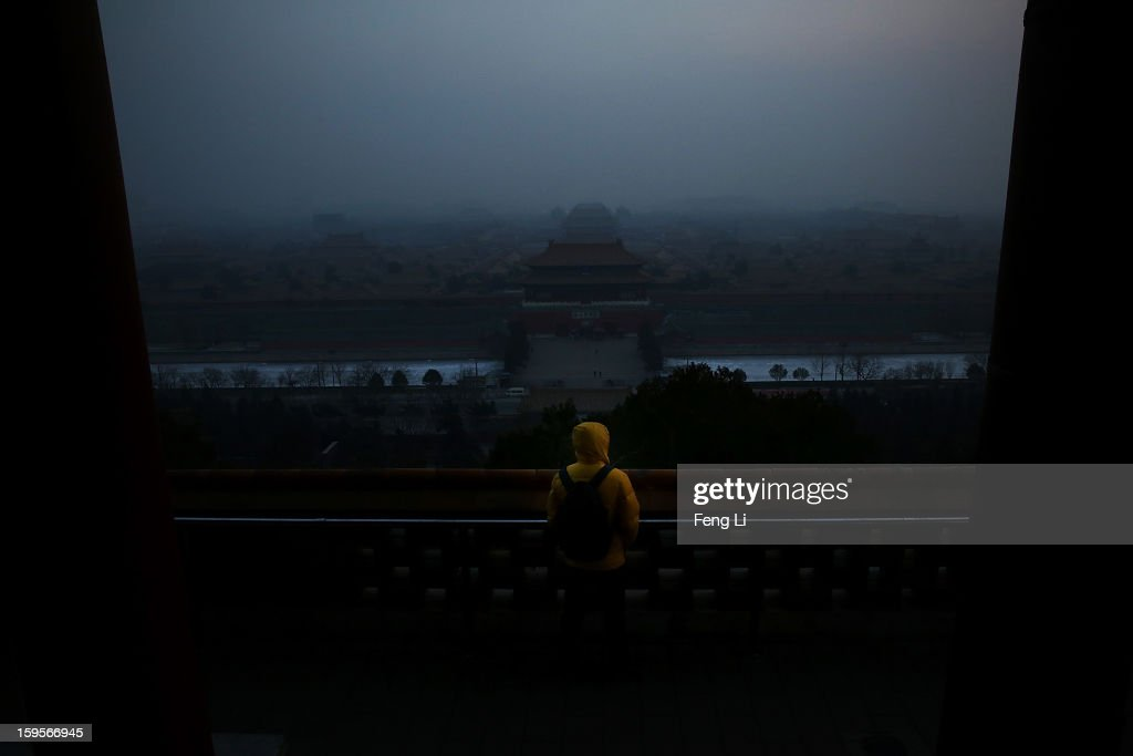 A tourist looks at the Forbidden City as pollution covers the city on January 16, 2013 in Beijing, China. Heavy smog shrouded Beijing with pollution at hazardous levels from January 12.