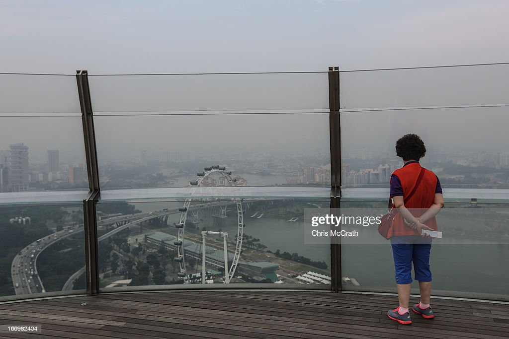 A tourist looks at the Singapore skyline covered in smoke haze from Marina Bay Sands Sky Park on April 19, 2013 in Singapore. The haze was created by burning off in neighbouring Sumatra and caused the Pollutant Standards Index to rise, hovering between 28 and 43.