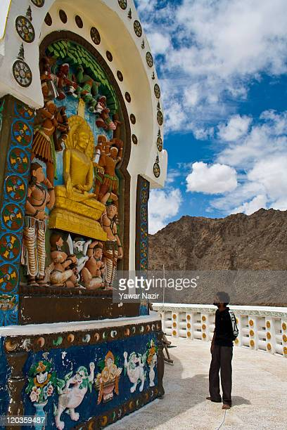 A tourist looks at the statue of Buddha in Shanti Stupa monastery on August 02 2011 in Leh east of Srinagar in Ladakh India Ladakh is a region within...