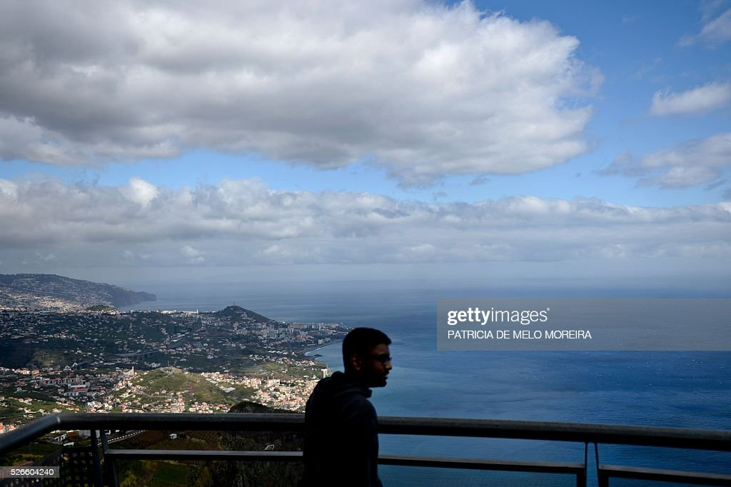 A tourist looks from a lookout of Cabo Girao in Camara de Lobos, Madeira island on April 30, 2016. / AFP / PATRICIA
