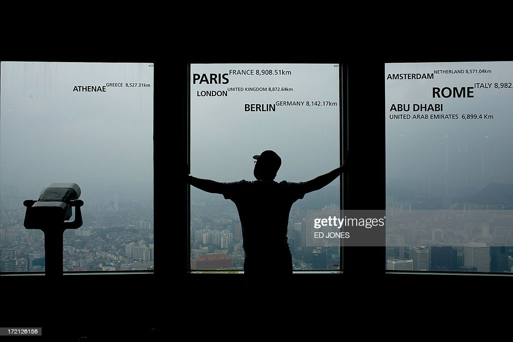 A tourist looks from a window of the Namsan tower overlooking the Seoul city skyline during rainfall on July 2, 2013. July marks the wet season for Seoul during which the city of10 million people receives some 60 percent of its annual rainfall. AFP PHOTO / Ed Jones