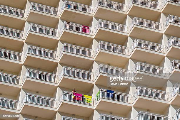 A tourist looks from the balcony of an apartment building at Magaluf beach on July 12 2014 in Mallorca Spain Magaluf is one of the Britain's favorite...