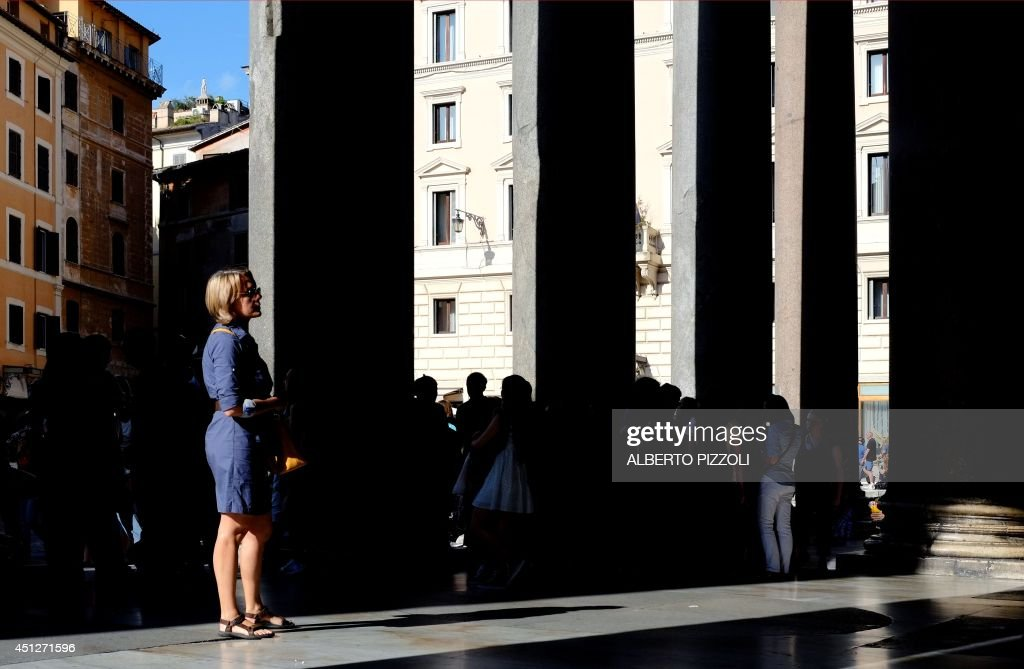 A tourist looks on as she stands near the colonnade of the Pantheon on June 26 , 2014 in Rome. Dating from 126 AD, the monument is the best preserved ancient building of the city.