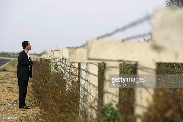 A tourist looks over the Chinese newly installed fence at North Korea on October 21 2006 in the Chinese border city of Dandong Liaoning Province of...