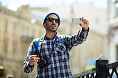 Young man making selfie while having walk in the city