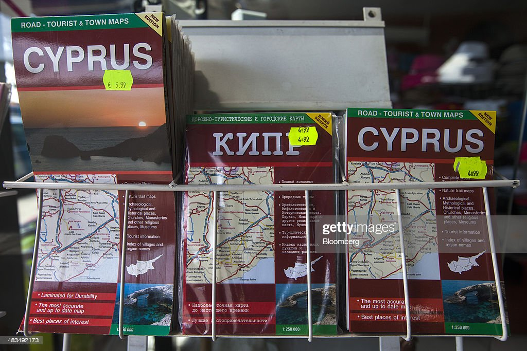 Tourist maps for Cyprus in Russian and English languages sit for sale outside a store in Limassol, Cyprus, on Tuesday, April 8, 2014. Cyprus wants to shield financial flows with Russia, where it's the biggest foreign investor, as the U.S. and the European Union ratchet up sanctions in response to President Vladimir Putin's annexing Crimea from Ukraine. Photographer: Andrew Caballero-Reynolds/Bloomberg via Getty Images