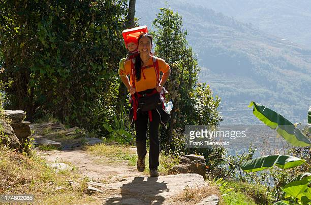 A tourist mother carrying her little child in a child carrier rucksack on her back on a trekking holiday
