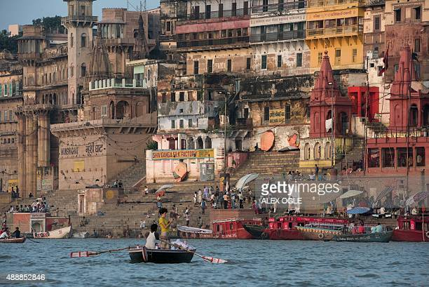 A tourist on a boat takes a photograph of the waterfront on the banks of the River Ganges at Varanasi on September 18 2015 The river is considered...