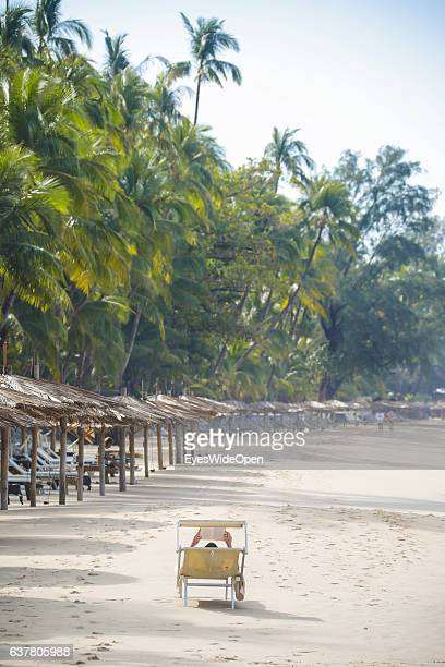 Tourist on a deck chair reading a book on the beach on December 13 2016 in Thandwe Ngapali Beach Myanmar