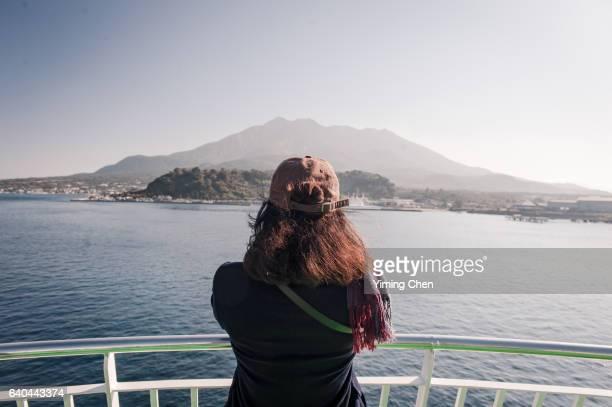 Tourist on Ferry Ship Looking at Sakurajima Volcano