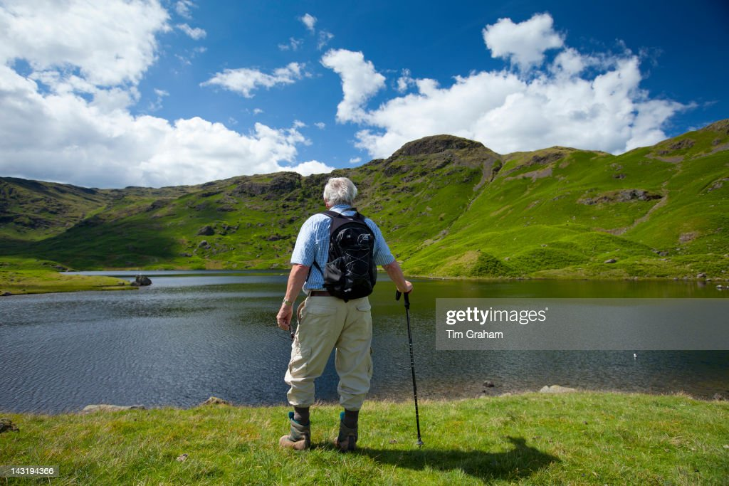 Tourist on nature trail in lakeland countryside at Easedale Tarn lake in the Lake District National Park, Cumbria, UK