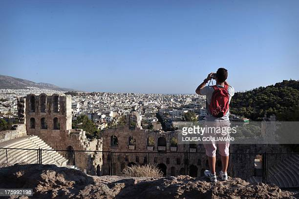 A tourist overhanging the ancient Acropolis in Athens watches with binoculars on August 11 2013 Germany's central bank expects Greece to receive...