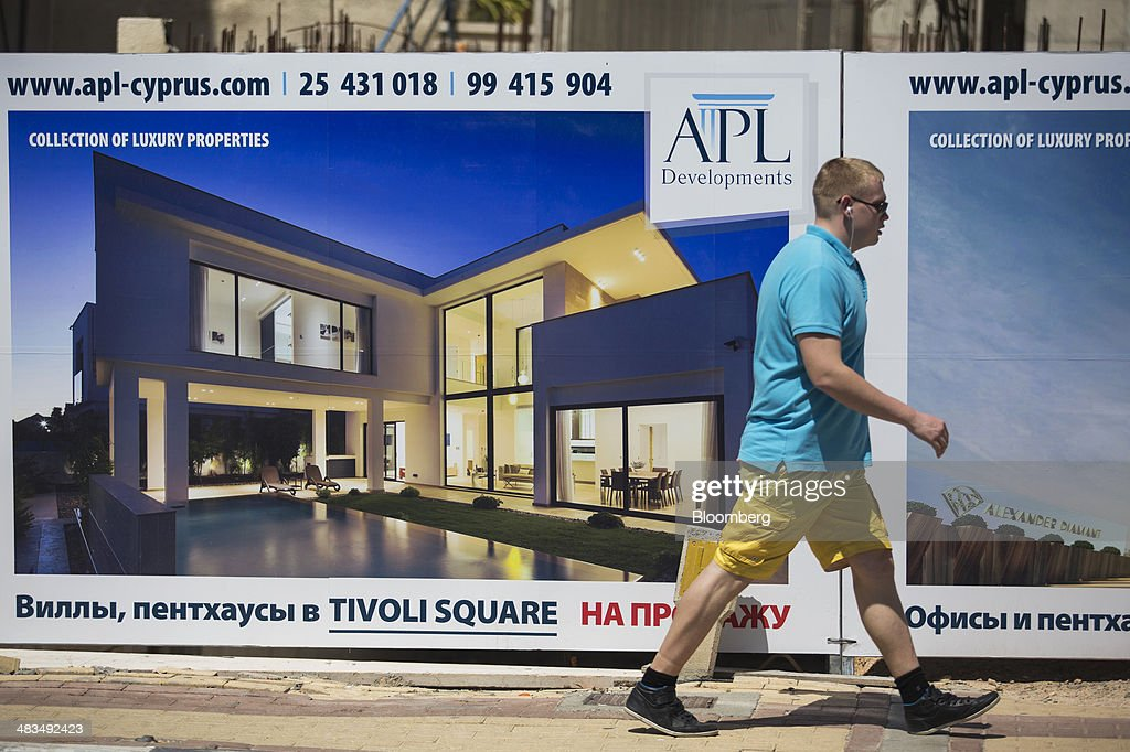 A tourist passes a billboard by the APL Group, advertising luxury property for sale in Russian cyrillic script in Limassol, Cyprus, on Tuesday, April 8, 2014. Cyprus wants to shield financial flows with Russia, where it's the biggest foreign investor, as the U.S. and the European Union ratchet up sanctions in response to President Vladimir Putin's annexing Crimea from Ukraine. Photographer: Andrew Caballero-Reynolds/Bloomberg via Getty Images