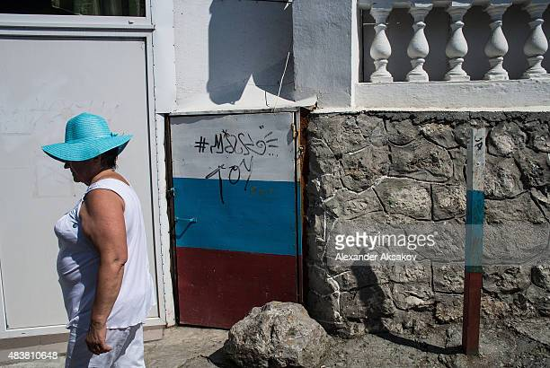 A tourist passes by a door colored in colors of Russian flag on August 11 2015 in Yalta Crimea Russian President Vladimir Putin signed a bill in...