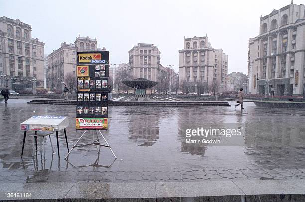 Tourist photographer's display board with Kodak and Polaroid in Independence Square in the rain Kiev November 1995