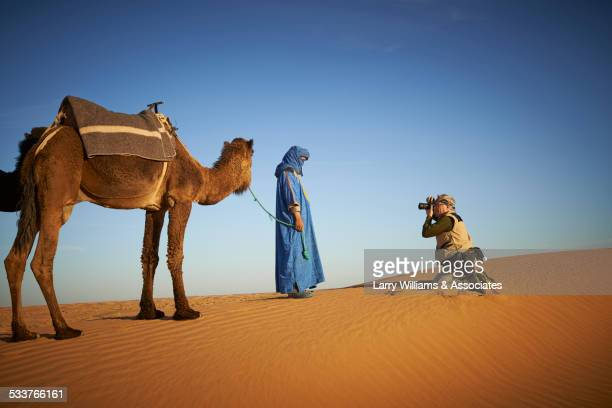Tourist photographing guide with camel on sand dune in desert landscape