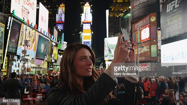 Tourist photographing iconic glowing billboard advertisements with cell phone in city intersection at night