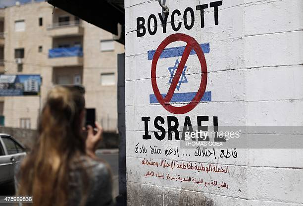 A tourist photographs a sign painted on a wall in the West Bank biblical town of Bethlehem on June 5 calling to boycott Israeli products coming from...