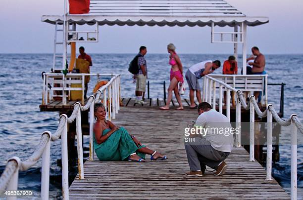 A tourist photographs a woman by the beach at the Egyptian Red Sea resort of Sharm elSheikh on November 2 2015 A Russian passenger plane carrying 224...