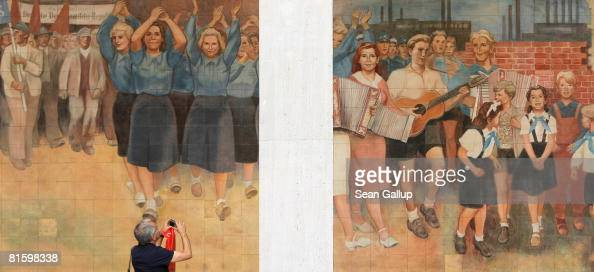 A tourist photographs an East German communistera socialist realist mural near a memorial to the 1953 East German workers' uprising on the 55th...