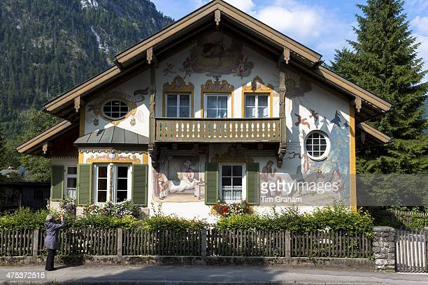 Tourist photographs painted facade of Grimms Fairy Tale Little Red Riding Hood in Oberammergau in Bavaria Germany
