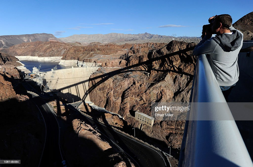 A tourist photographs the Hoover Dam from the pedestrian walkway on the Mike O'Callaghan-Pat Tillman Memorial Bridge part of the Hoover Dam Bypass Project October 26, 2010 in the Lake Mead National Recreation Area, Nevada. The 1,900-foot-long structure sits 890 feet above the Colorado River, about a quarter of a mile downstream from the Hoover Dam. The USD 240 million four-lane bypass project to relieve vehicle traffic on the Hoover Dam began in 2003, and opened to traffic on October 19.