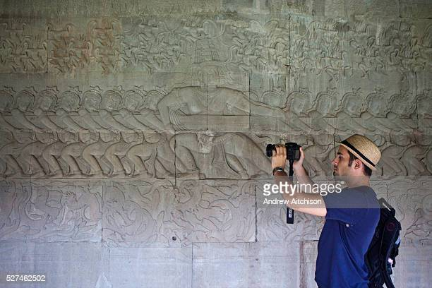 A tourist photographs the Samudra manthan or the churning of the ocean milk on the North Corridor wall at the Angkor Wat Temple in Cambodia  ...