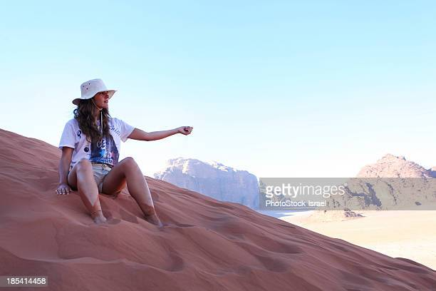 tourist plays with sand on a sand dune