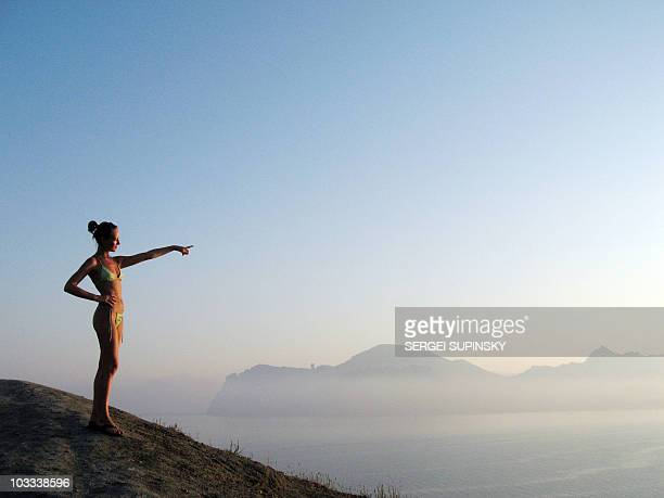 A tourist points as she enjoys a view during sunset from atop a hill near the popular Ukrainian Black Sea resort of Koktebel Crimea on August 1 2010...