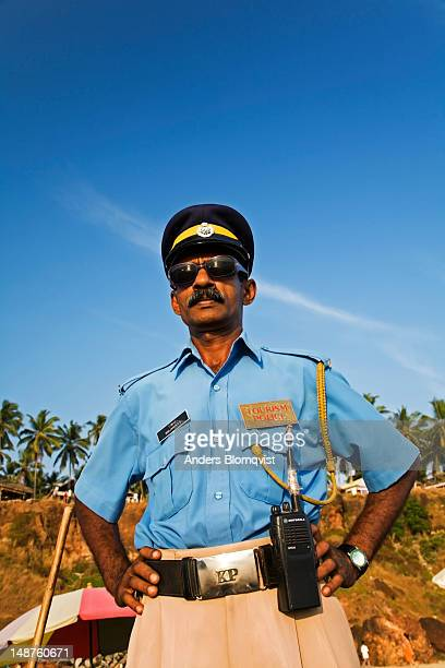 Tourist policeman on beach wearing sunglasses.
