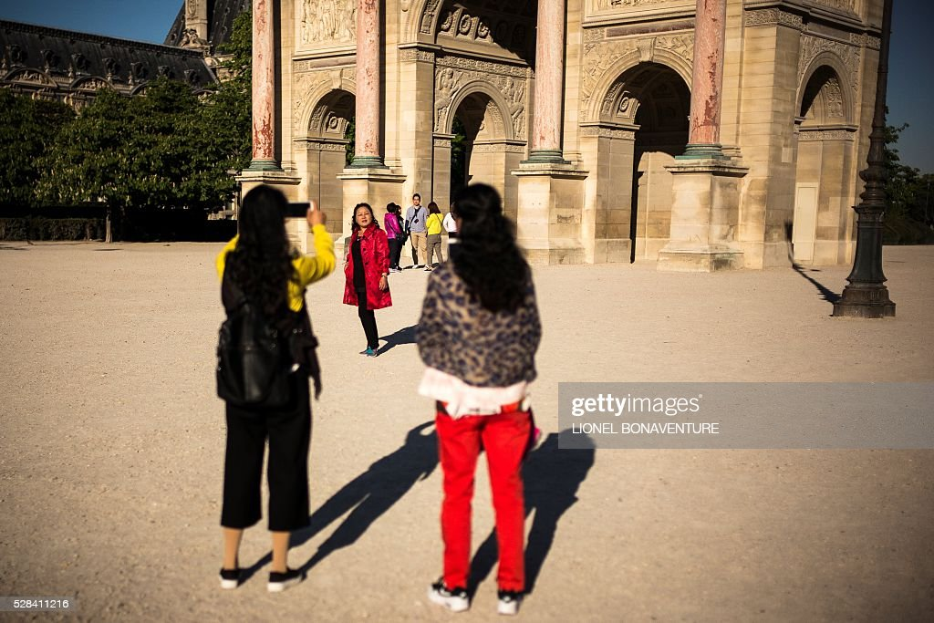 A tourist pose for a picture at the Tuileries garden on May 5, 2016 in Paris. / AFP / LIONEL