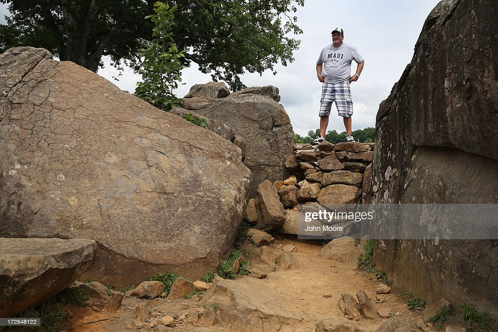 A tourist poses as a relative photographs him at Devil's Den on July 2, 2013 in Gettysburg, Pennsylvania. Many tourists visiting the historic site pose for photos there as part of their battlefield experience. An historic photo entitled 'The Home of a Rebel Sharpshooter' was taken there by Alexander Gardner on July 5, 1863 and featured a dead Confederate soldier. The photograph was later discovered to be staged, the dead body of the 'sharpshooter' having been brought from another place on the battlefield for the photograph and the gun not a sharps rifle.