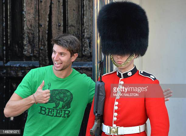 A US tourist poses for a photo with a soldier from the Queen's Guards outside St James Palace in central London on July 26 2012 British Prime...