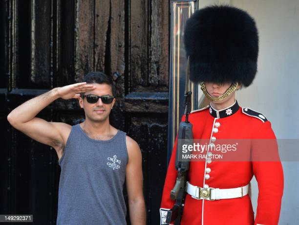 A tourist poses for a photo with a soldier from the Queen's Guards outside St James Palace in central London on July 26 2012 British Prime Minister...