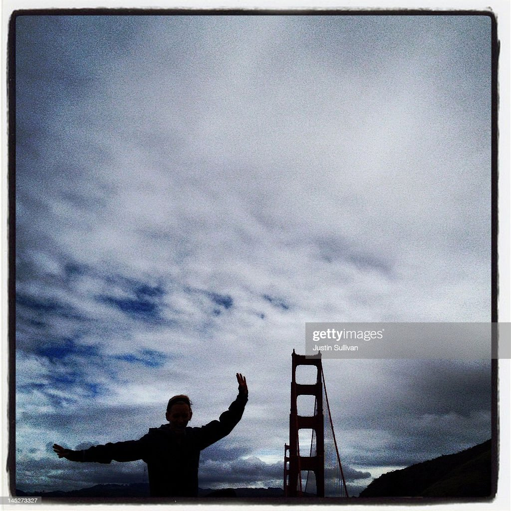 A tourist poses for a photograph near the Golden Gate Bridge on May 3, 2012 in San Francisco, California. The Golden Gate Bridge, Highway and Transportation District is preparing for the 75th anniversary of the iconic Golden Gate Bridge that will be marked with a festival on May 26 - 27 that will feature music, displays of bridge artifacts and art exhibits. The 1.7 mile steel suspension bridge, one of the modern Wonders of the World, opened to traffic on May 27, 1937.
